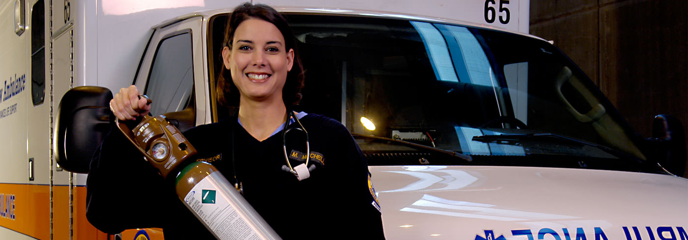 Medical personnel holding a cylinder standing by an ambulance
